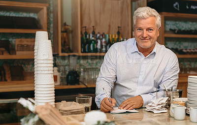 Buy stock photo Cropped portrait of a mature male entrepreneur writing down orders while standing in his self-owned coffee shop