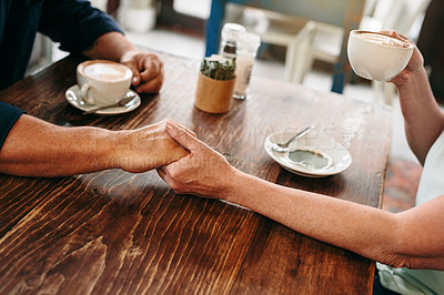 Buy stock photo High angle shot of an unrecognizable mature couple holding hands while enjoying their date in a coffee shop
