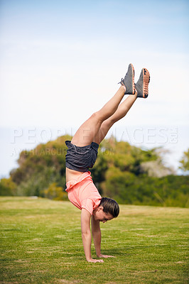 Buy stock photo Shot of a young attractive woman doing a handstand outside