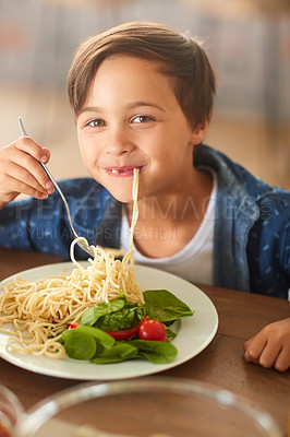 Buy stock photo Cropped shot of an adorable little boy eating his food at home