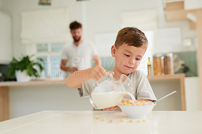 Buy stock photo Shot of an adorable little boy having breakfast with his father in the background at home