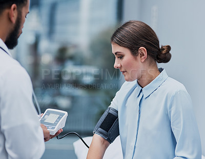 Buy stock photo Shot of a doctor checking a patient's blood pressure