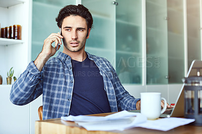 Buy stock photo Shot of a focused young man talking on his phone while working inside at home