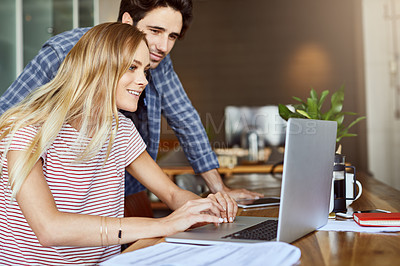 Buy stock photo Shot of a cheerful young couple working together on a laptop while being seated next to table at home
