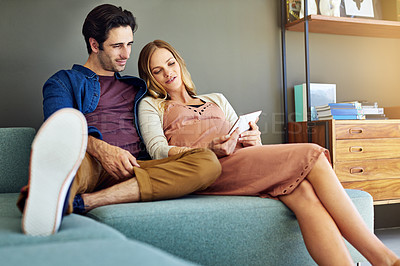 Buy stock photo Shot of a young man and his pregnant wife using a digital tablet together on the sofa