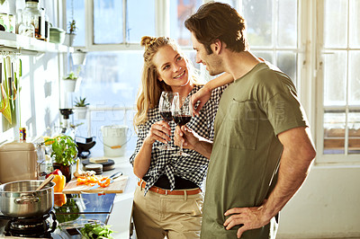 Buy stock photo Shot of a young couple drinking wine while preparing a meal together at home