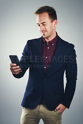 Buy stock photo Studio shot of a confident young businessman using a mobile phone against a gray background