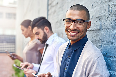 Buy stock photo Portrait of a businessman using a cellphone with his colleagues in the background outdoors