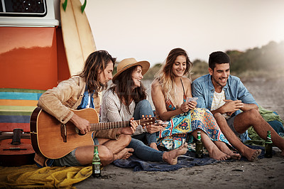 Buy stock photo Cropped shot of a group of friends hanging out together on the beach