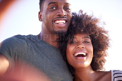 Buy stock photo Cropped shot of a young attractive couple taking a selfie while spending time together at the beach