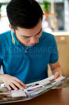 Buy stock photo Shot of a confident young man browsing through a menu at a restaurant deciding what to order inside during the day