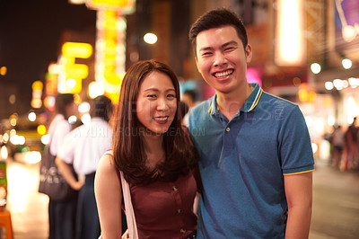 Buy stock photo Shot of a happy young couple enjoying a night out in the city