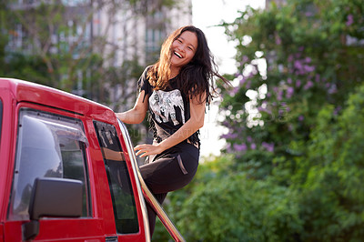 Buy stock photo Cropped portrait of an attractive young woman on the back of a truck while enjoying a roadtrip