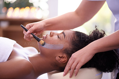 Buy stock photo Shot of a young woman getting a facial treatment at a spa