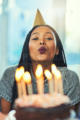 Buy stock photo Cropped shot of an attractive young woman blowing out her birthday candles