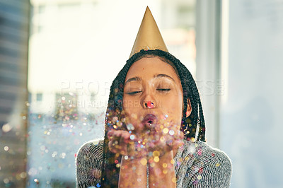 Buy stock photo Cropped shot of an attractive young woman blowing confetti while celebrating at a birthday party