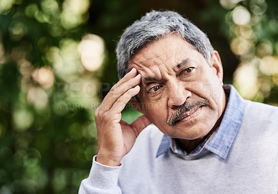 Buy stock photo Shot of a mature man looking worried outdoors