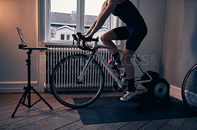 Buy stock photo Cropped shot of an unrecognizable woman working out on an exercise bike at home