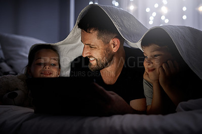 Buy stock photo Shot of a father and his two little children using a digital tablet together in bed at night