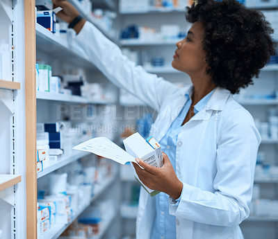 Buy stock photo Shot of a young pharmacist filling a prescription at a chemist