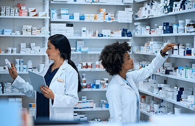 Buy stock photo Shot of two young women doing inventory in a pharmacy