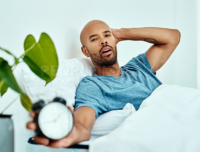 Buy stock photo Cropped shot of a man holding up his alarm clock while lying in bed