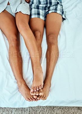 Buy stock photo Cropped shot of an unrecognizable couple lying on their bed