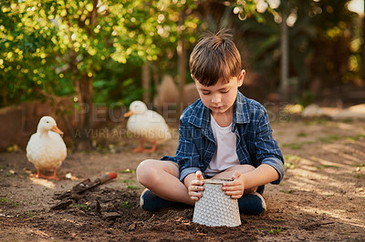 Buy stock photo Shot of an adorable little boy playing in the sand outside