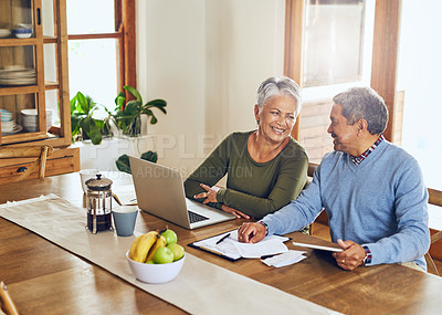 Buy stock photo Shot of a mature couple managing their paperwork together at home