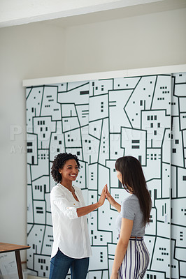 Buy stock photo Shot of two young businesswomen giving each other a high five in a modern office