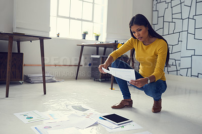Buy stock photo Shot of a young businesswoman working through paperwork in a modern office