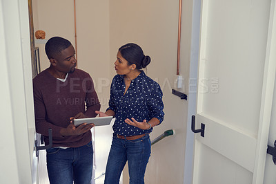 Buy stock photo Shot of a young businessman and businesswoman using a digital tablet together in a modern office