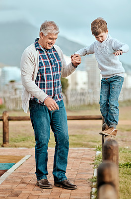 Buy stock photo Full length shot of an adorable little boy holding his grandfather's hand while walking on a wooden railing outside