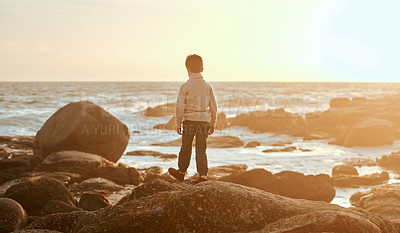 Buy stock photo Rearview shot of an adorable little boy walking on the beach