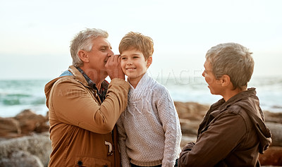 Buy stock photo Cropped shot of a senior man whispering something into his grandson's ear at the beach