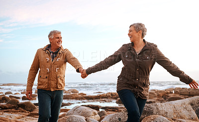 Buy stock photo Cropped shot of a senior woman leading her husband by the hand while walking on the beach