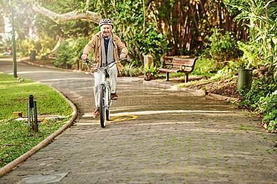 Buy stock photo Shot of a senior man riding his bicycle through a park