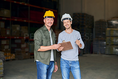 Buy stock photo Cropped portrait of two male construction workers looking over some paperwork while standing in an industrial warehouse