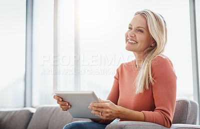Buy stock photo Shot of an attractive mature woman using a digital tablet while relaxing on the sofa at home