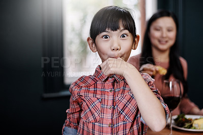 Buy stock photo Portrait of an adorable little girl licking her fingers while having a meal at home