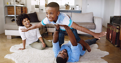 Buy stock photo Shot of a young family spending time together in the living room a home
