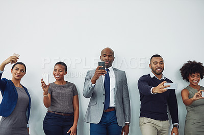 Buy stock photo Cropped shot of a group of businesspeople taking selfies while waiting in line for their interview