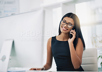 Buy stock photo Shot of a young businesswoman talking on her phone while sitting at her desk