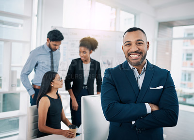 Buy stock photo Shot of a businessman in an office with his colleagues in the background