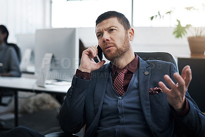Buy stock photo Shot of a mature businessman using a mobile phone in a modern office