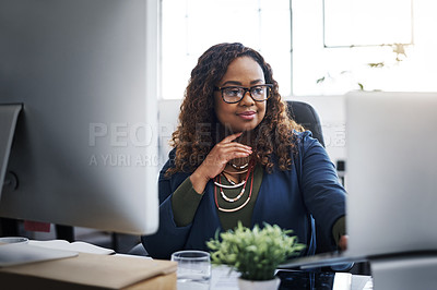Buy stock photo Shot of a young businesswoman using a laptop at her desk in a modern office