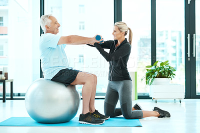 Buy stock photo Shot of a physiotherapists helping her senior patient with his exercises in a fitness center