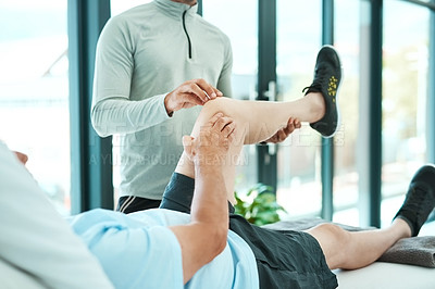Buy stock photo Shot of a senior man consulting with his physiotherapist