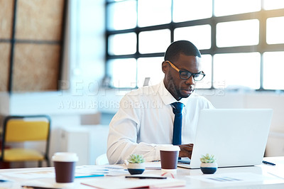 Buy stock photo Shot of a focused young businessman typing on his laptop while being seated at his desk in the office at work during the day