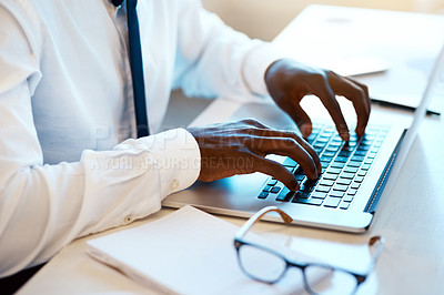 Buy stock photo Closeup of an unrecognizable man working and typing on his laptop at his desk with his reading glasses placed next to him in the office during the day